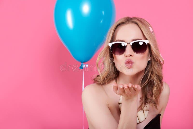 典雅的晚礼服和金黄首饰的可爱的白肤金发的少妇庆祝生日和送往照相机的一个飞吻 免版税库存照片