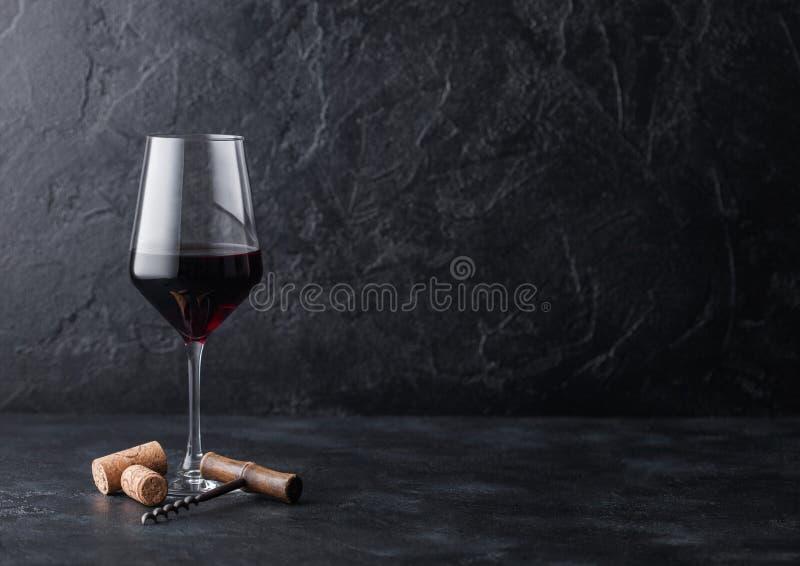 典雅的杯与黄柏的在黑石背景的红酒和拔塞螺旋 自然光 免版税库存图片