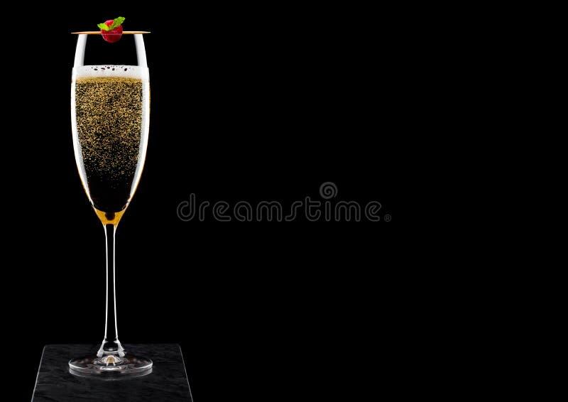 典雅的杯与rasspbery的黄色香槟在黑人大理石委员会的棍子黑背景的 免版税图库摄影
