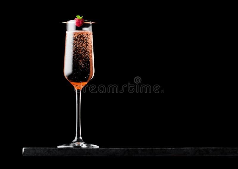 典雅的杯桃红色玫瑰色香槟用在棍子的莓在黑背景的黑人大理石委员会 r 免版税库存图片