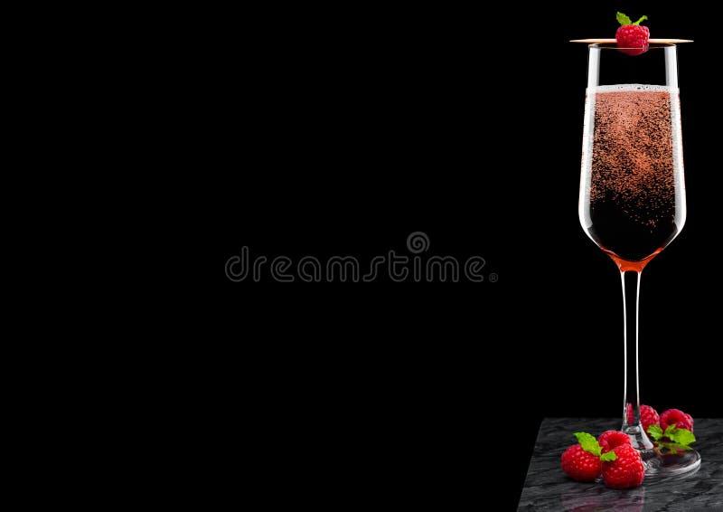 典雅的杯桃红色玫瑰香槟用在棍子的莓用新鲜的莓果和薄荷的叶子在黑人大理石委员会黑backg的 库存照片