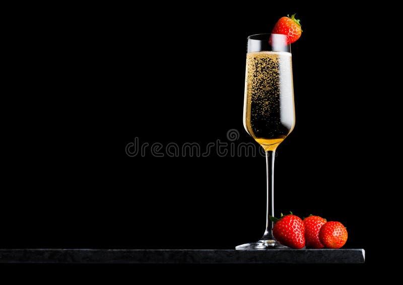 典雅的杯黄色香槟用在顶面和新鲜的莓果的草莓在黑背景的黑人大理石委员会 te的空间 库存图片