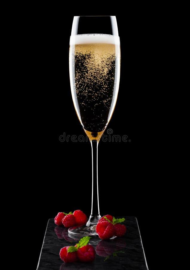 典雅的杯黄色香槟用莓和新鲜的莓果与薄荷的叶子在棍子在黑人大理石委员会黑backgrou的 库存照片