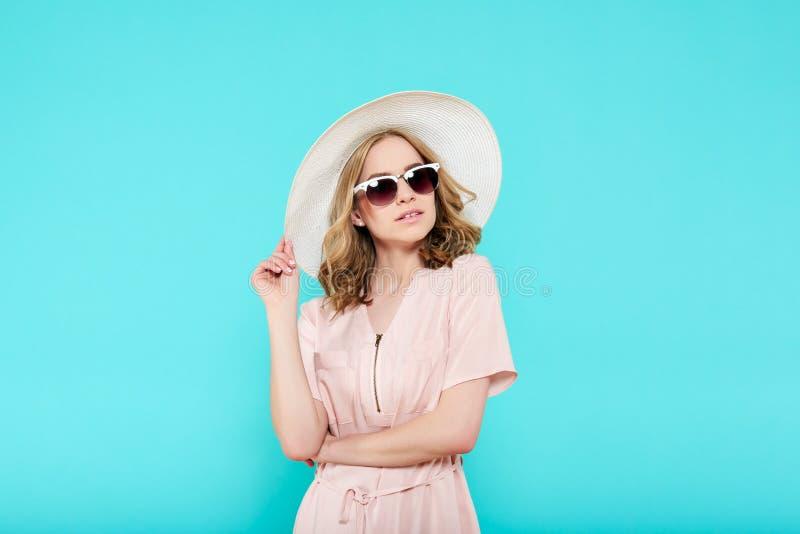 典雅的淡粉红的礼服、太阳镜和夏天帽子的美丽的少妇 时髦的女人演播室画象  库存图片