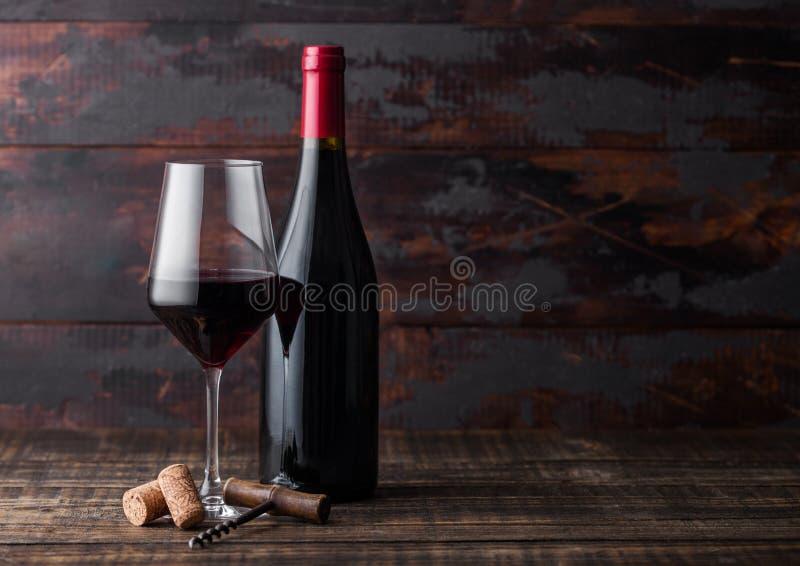 典雅的玻璃和瓶与黄柏的在黑暗的木背景的红酒和拔塞螺旋 自然光 免版税库存照片