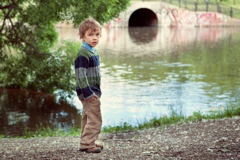 典雅的男孩在河河岸突出  免版税库存图片