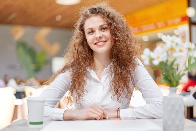 典雅的白色女衬衫的华美的可爱的卷曲少妇,有卷曲分蘖性头发,在咖啡店的recreats与拿走咖啡 免版税库存图片