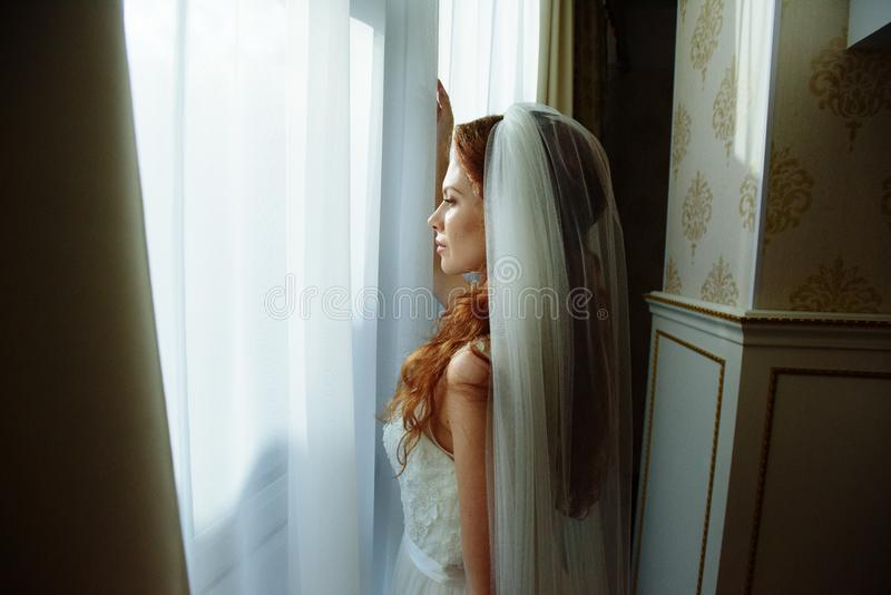 典雅的白色婚礼礼服的美丽的性感的redhair夫人 户内模型时尚画象  站立远离风的秀丽妇女 免版税图库摄影