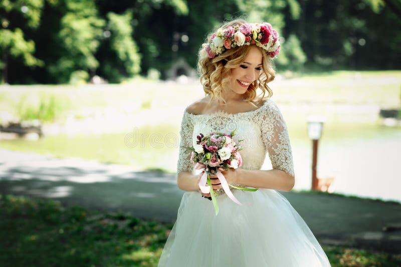 典雅的白色礼服的美丽的白肤金发的愉快的新娘在花圈 图库摄影