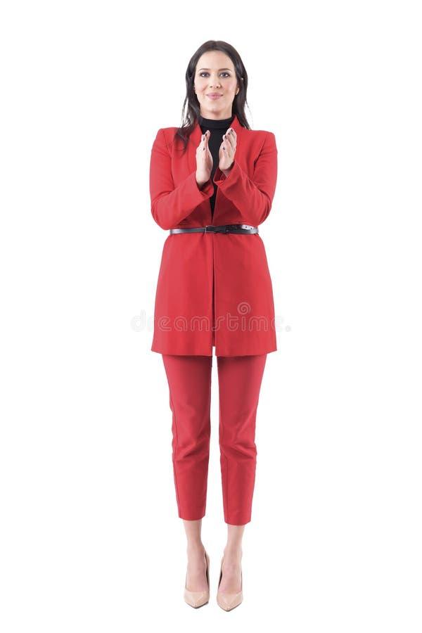 典雅的红色衣服的年轻女商人祝贺和鼓掌在起立欢呼的 库存照片