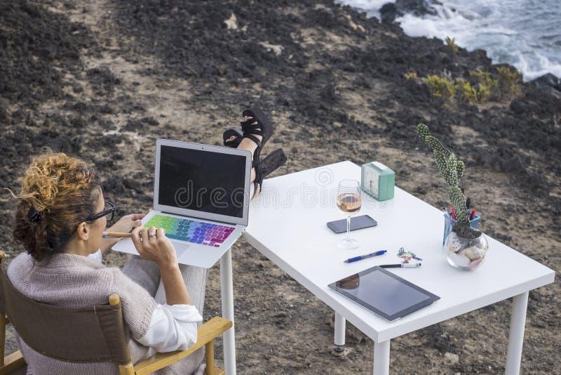 典雅的经理妇女白种人的供选择的办公室企业地方与技术现代膝上型计算机一起使用在前面 免版税库存照片