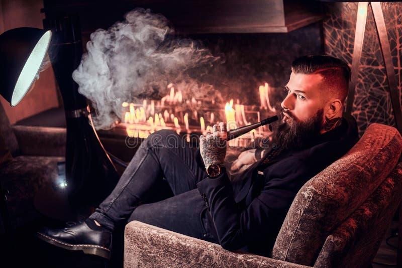 典雅的聪明的人是放松和抽水烟筒在长的辛苦以后 免版税库存照片