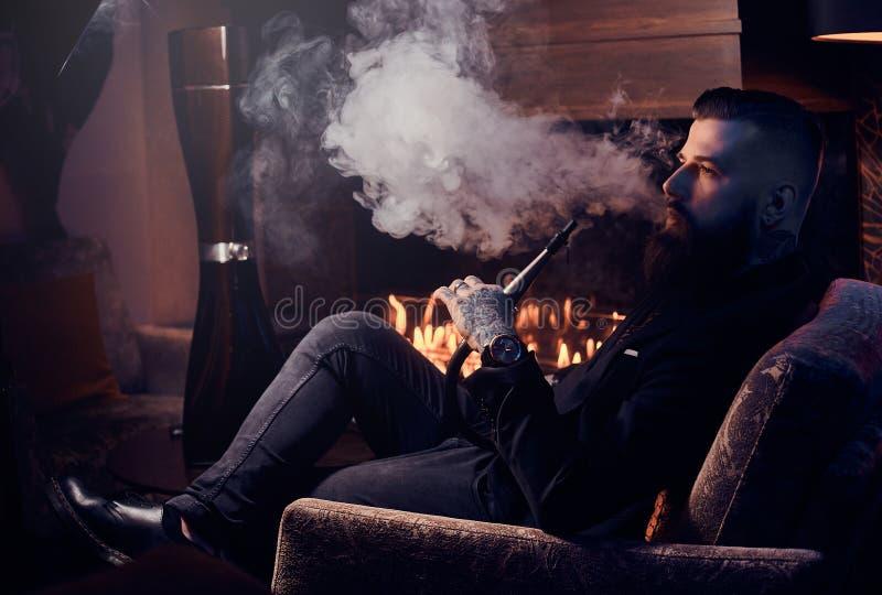 典雅的聪明的人是放松和抽水烟筒在长的辛苦以后 库存图片