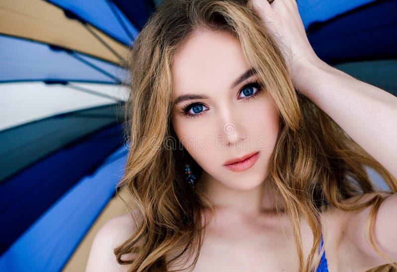 典雅的蓝色内裤和胸罩的美丽的性感的夫人 户内模型时尚画象  拿着伞的秀丽白肤金发的妇女 f 库存照片
