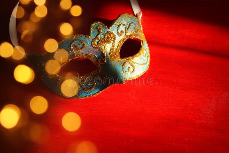 典雅的蓝色和金威尼斯式面具的图象在红色背景的 库存图片