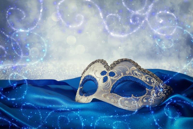 典雅的蓝色和金威尼斯式面具的图象在蓝色丝绸fabr的 库存照片