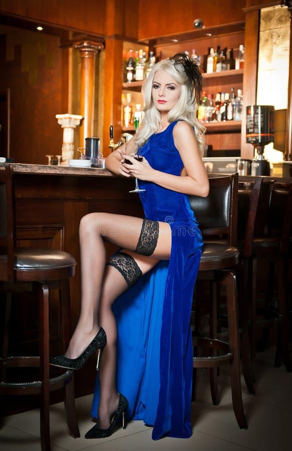 典雅的蓝色长的礼服的可爱的白肤金发的妇女坐高凳在她的手上的拿着一块玻璃。华美的白肤金发的模型 免版税库存图片
