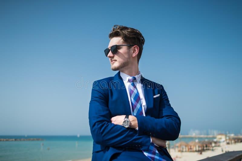 典雅的衣服的年轻严肃的在海的背景的人和sunglass 库存图片
