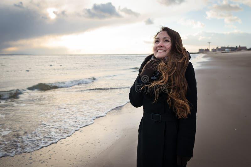 典雅的衣裳的年轻愉快的俏丽的妇女在NYC的冬天海滩 图库摄影