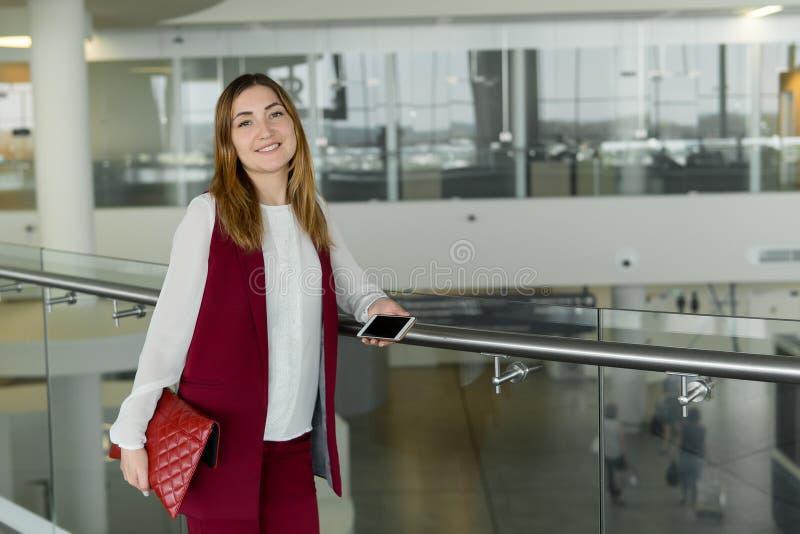 典雅的衣裳立场的女孩和输入智能手机在机场 免版税图库摄影