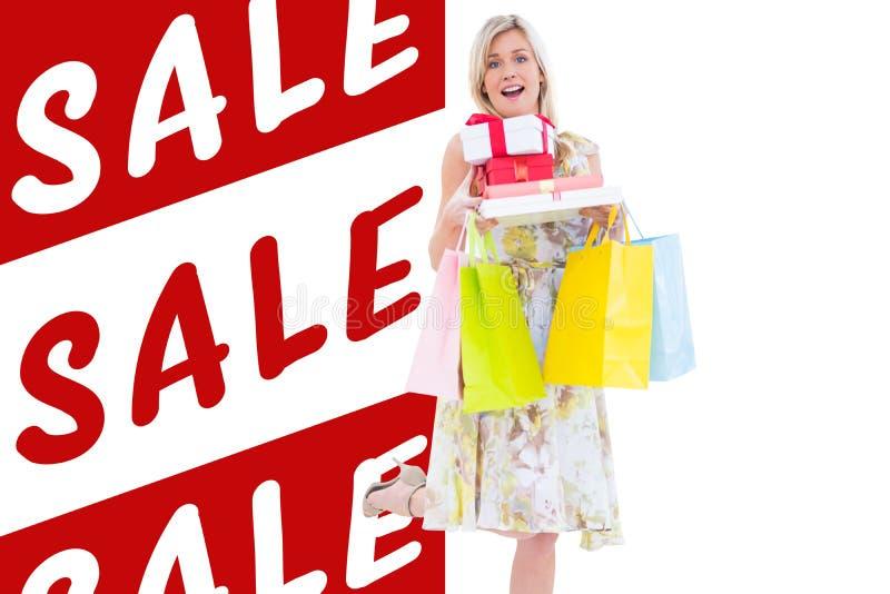 典雅的金发碧眼的女人的综合图象有购物袋和礼物的 免版税库存图片