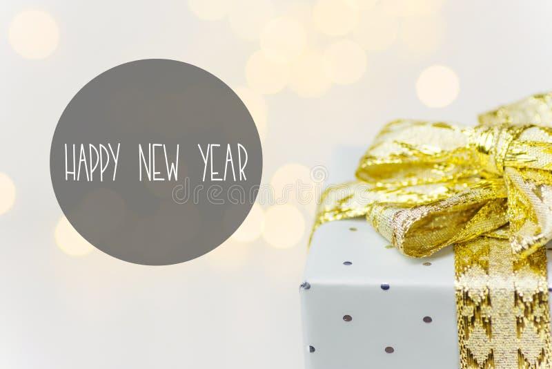 典雅的银色礼物盒栓与与弓bokeh诗歌选光的金黄丝带在白色背景 新年好贺卡 免版税库存图片