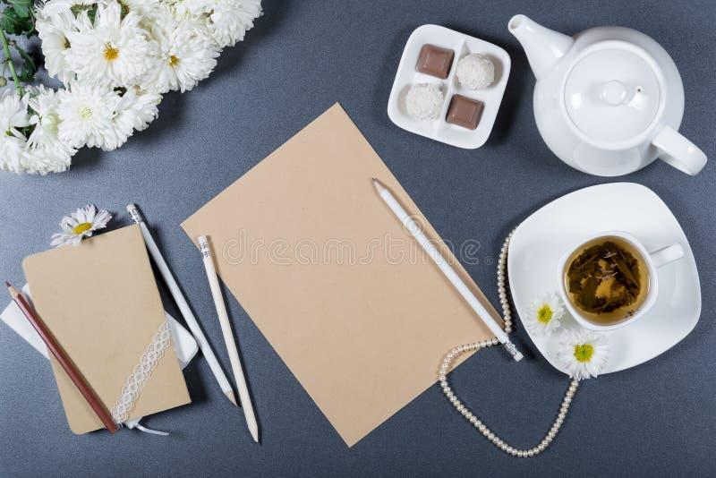 典雅的静物画-棕色工艺纸,笔记本,白色菊花,铅笔,茶壶,杯子板料清凉茶 免版税图库摄影