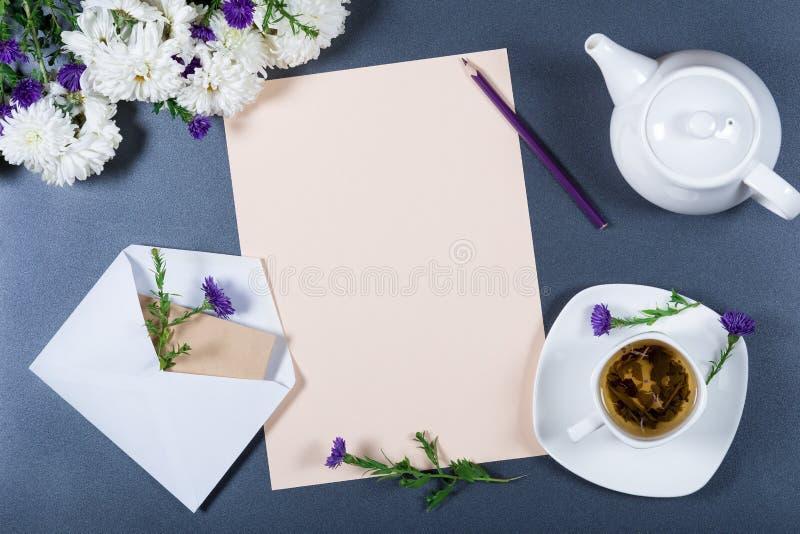 典雅的静物画-纸片、白色和紫色菊花、铅笔、茶壶、在灰色书桌上的杯子清凉茶和信封 免版税库存照片