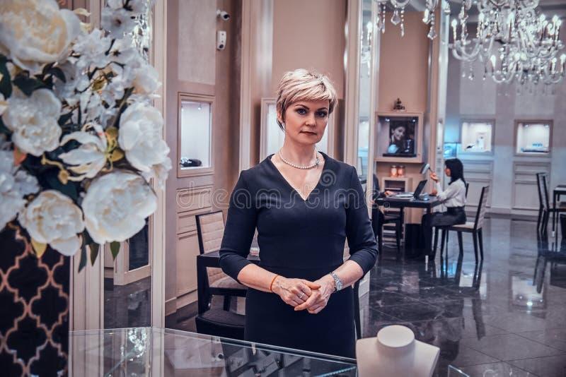 典雅的首饰精品店的所有者在她美丽的毫华商店等待顾客 库存图片