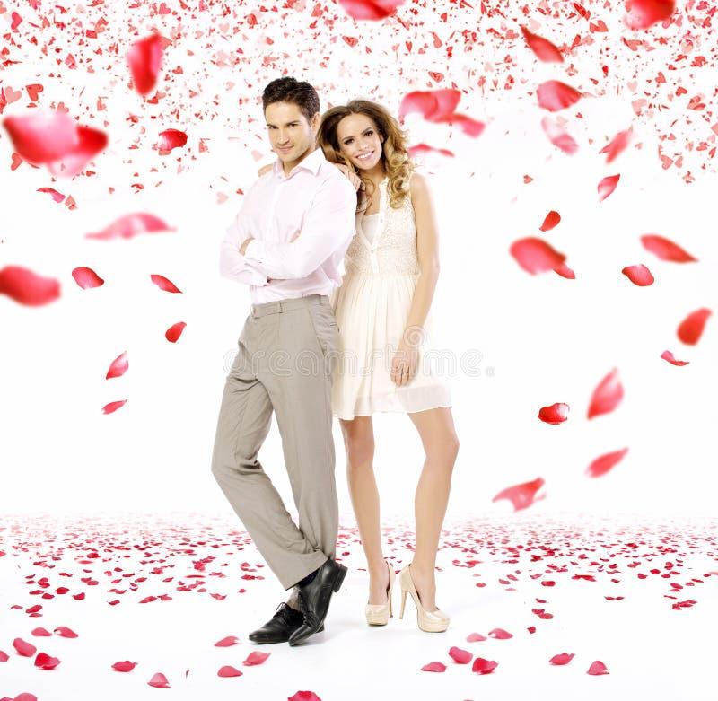 典雅的年轻夫妇在瓣雨中 免版税库存图片