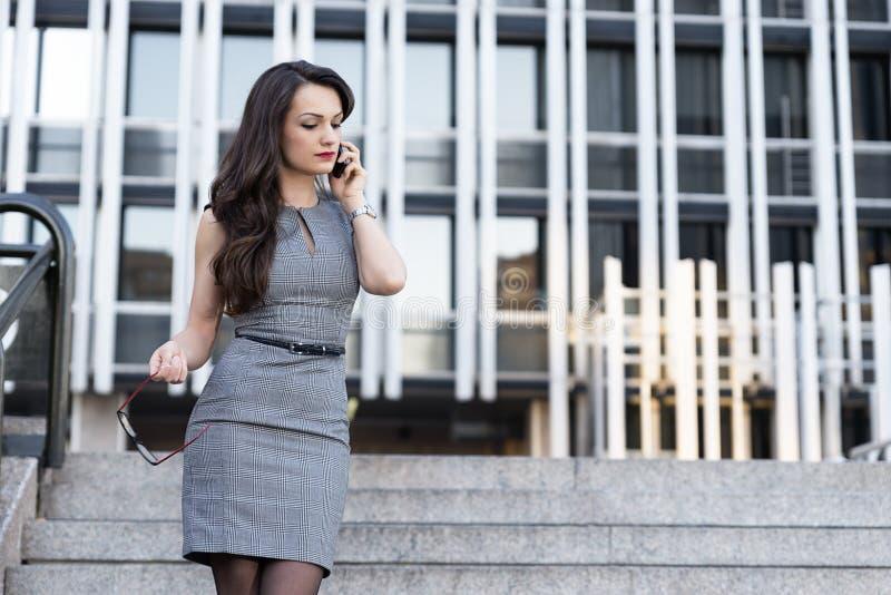 典雅的年轻女实业家谈话由电话 免版税库存图片