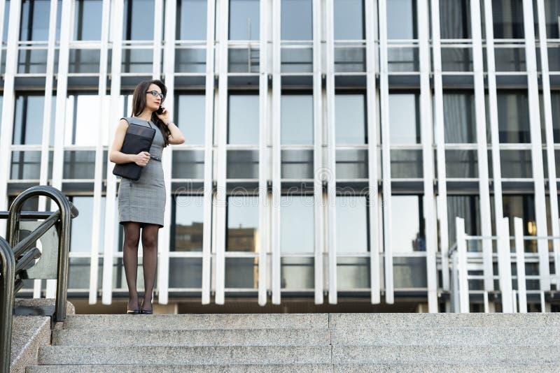 典雅的年轻女实业家谈话由电话 库存图片