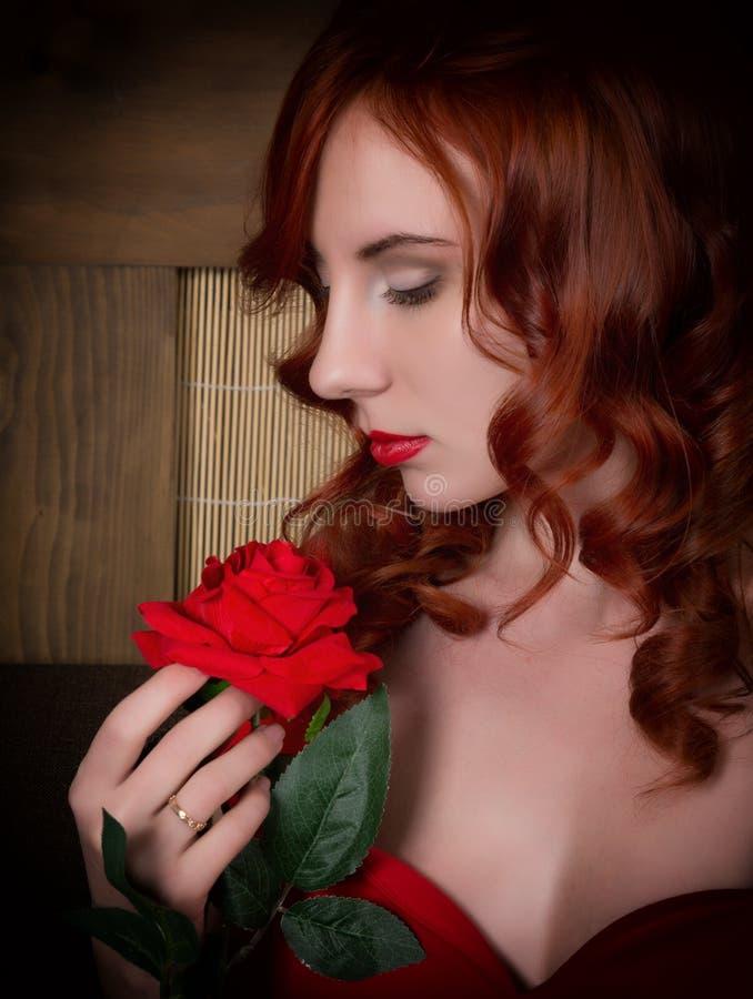 典雅的年轻红头发人妇女特写镜头画象一件红色礼服的,拿着一朵红色玫瑰 库存图片