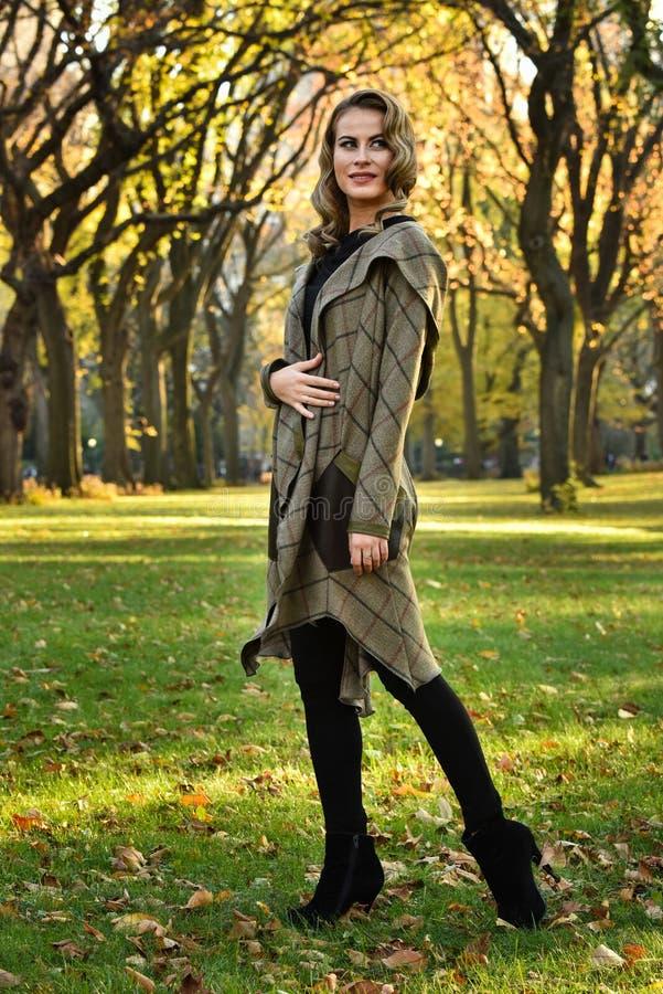 典雅设计外套走的妇女室外反对秋天自然风景 库存照片
