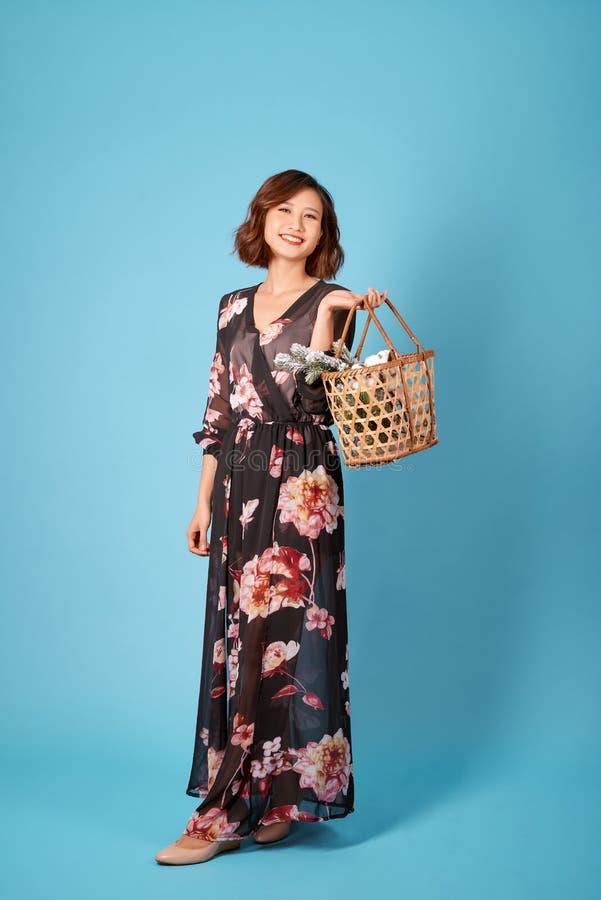 典雅,时髦夏天,春天成套装备街头时尚细节:秸杆篮子袋子在妇女的手上 免版税库存照片