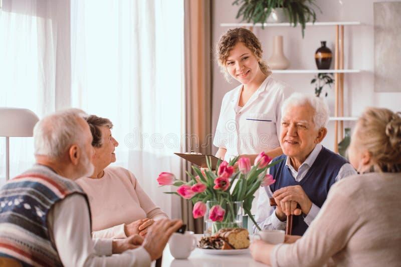 养老院的领抚恤金者谈话在下午快餐期间 免版税库存图片