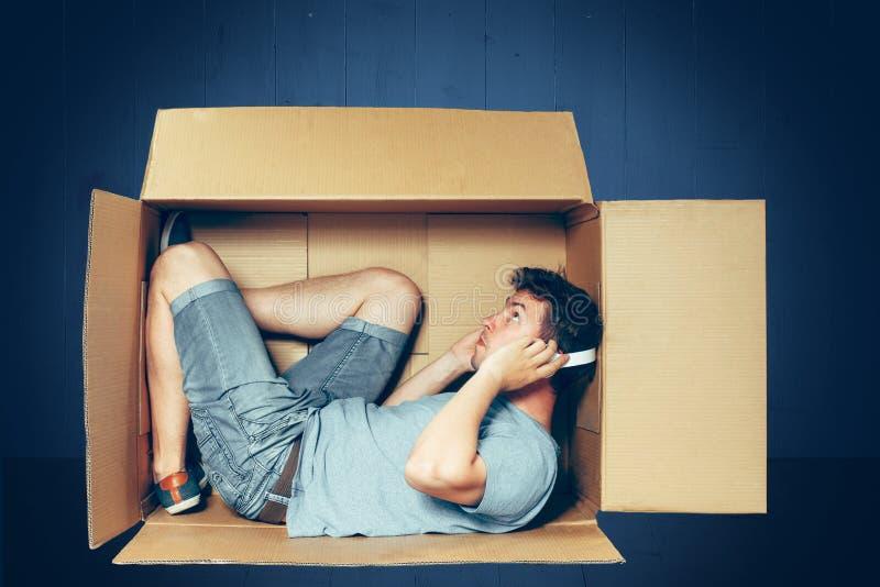 内向概念 人坐在箱子里面和与膝上型计算机一起使用 库存图片