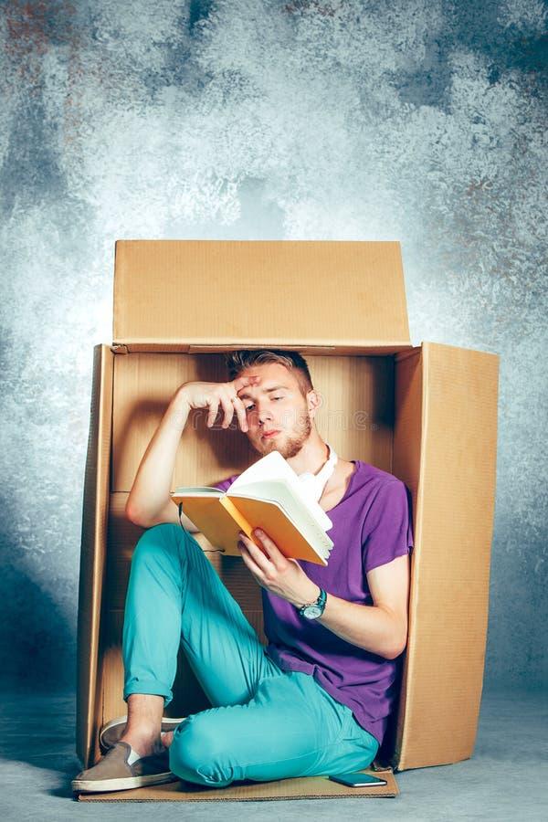 内向概念 坐在箱子和阅读书里面的人 库存照片