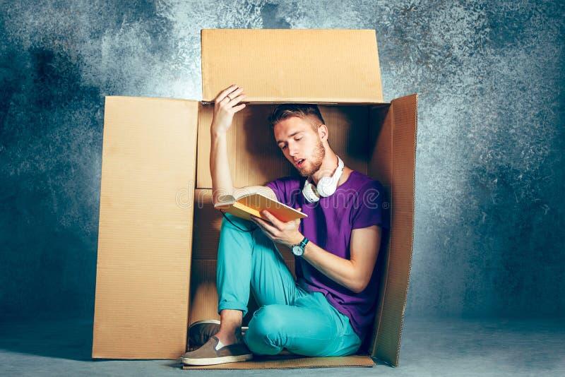 内向概念 坐在箱子和阅读书里面的人 免版税库存图片