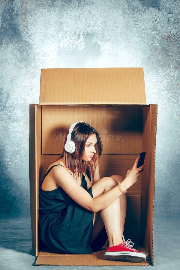 内向概念 妇女坐在箱子里面和与电话一起使用 库存图片