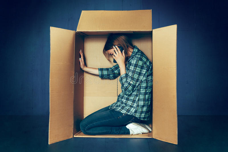 内向概念 妇女坐在箱子里面和与电话一起使用 免版税库存照片