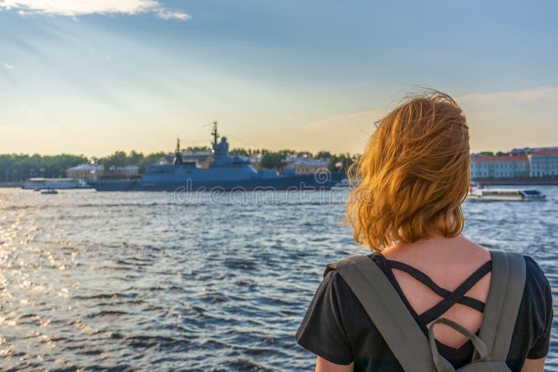 内娃看军舰和建筑合奏的河堤防的红头发人非离子活性剂旅游女孩在夏天晚上日落 图库摄影