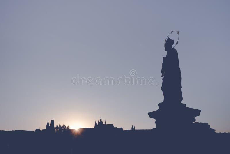 内波穆克的雕象的圣约翰剪影在查理大桥的在有圣维塔斯大教堂的布拉格在日落的背景中 免版税库存照片
