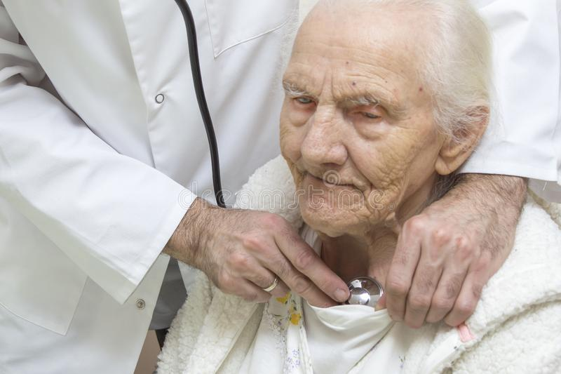 内科医生医生的手审查一个非常老妇人的肺有听诊器的 免版税库存图片