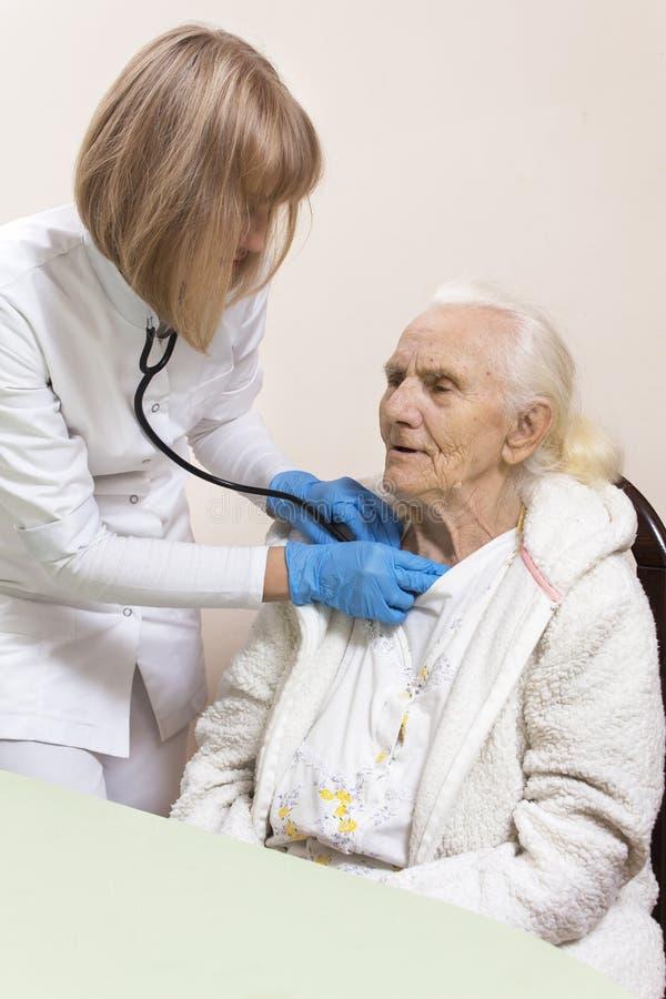 内科医生医生的手审查一个非常老妇人的肺有听诊器的 库存照片