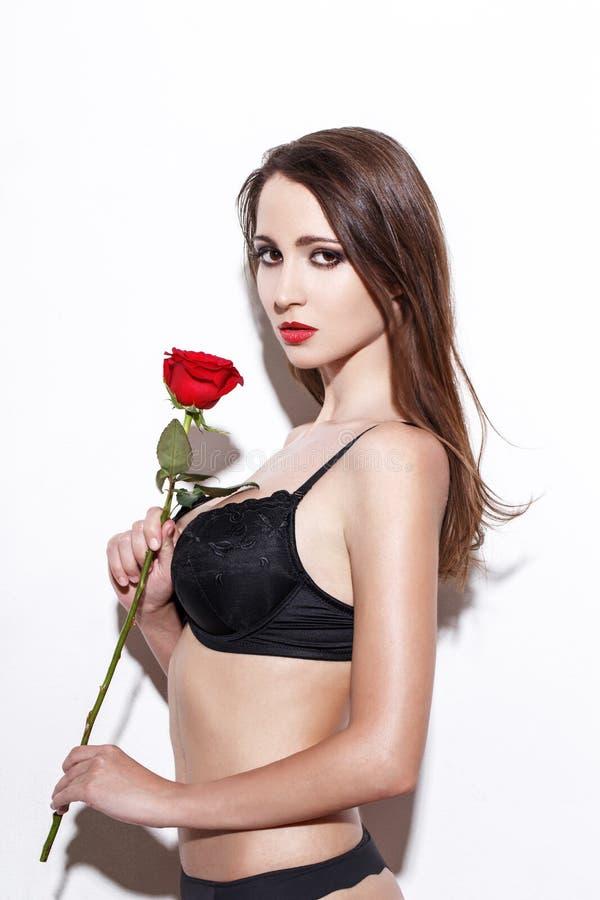 黑内衣的性感的深色的妇女有红色玫瑰的 免版税库存照片