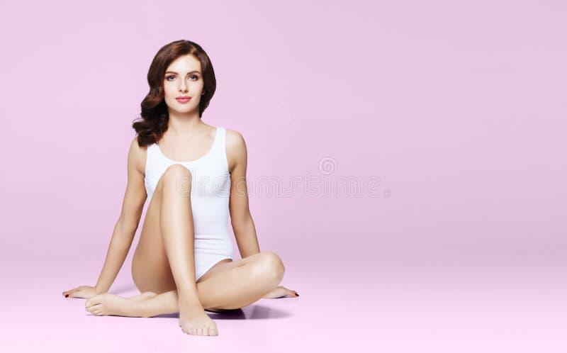 内衣的适合和运动的女孩 摆在白色泳装的美丽和健康妇女 免版税库存照片