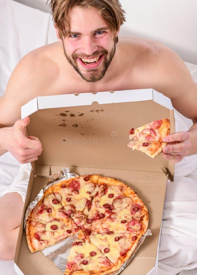 内衣的饥饿的年轻人在家坐与比萨箱子的一张床 谁对饮食关心 E 免版税库存照片