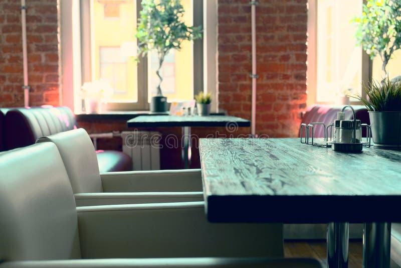 内部咖啡馆桌和椅子 被弄脏的背景用viitaniementie,背景与bokeh的迷离咖啡馆做了 库存图片