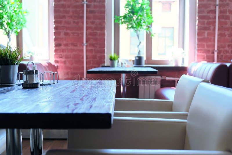 内部咖啡馆桌和椅子 被弄脏的背景用viitaniementie,背景与bokeh的迷离咖啡馆做了 库存照片